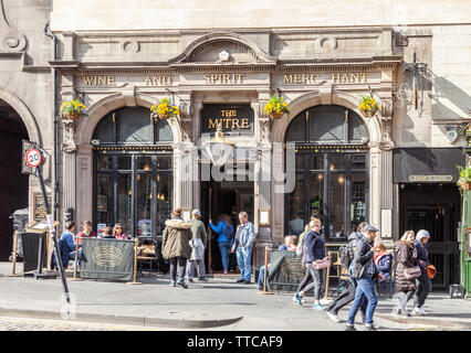 Cusomers outside and pedestrians passing the Mitre Bar, a city centre pub in the Royal Mile in the Old Town area of Edinburgh, Scotland, UK - Stock Photo