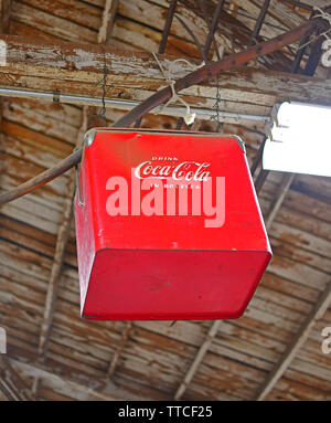 Classic red Coca-Cola cooler hanging from the rafters of a hardware store - Stock Photo