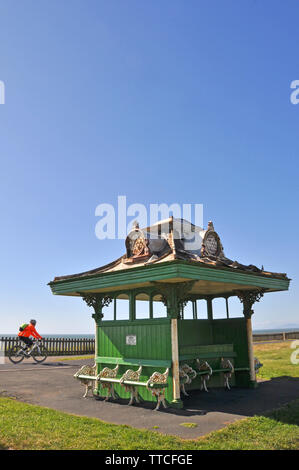 Victorian Blackpool beach shelter and cyclist on promenade, north shore near Bispham - Stock Photo