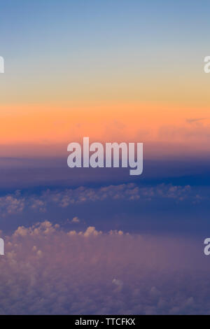 Beautiful sunset sky above clouds with dramatic light. Cabin view from airplane - Stock Photo
