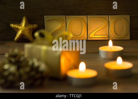 Golden new year 2020 greeting card with candles and gift - Stock Photo