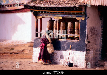 Tibetan woman in traditional clothing spinning prayer wheels,Palcho Chode monastery,Gyantse,Tibet - Stock Photo