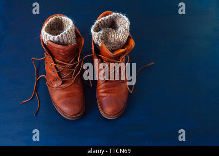 Old red dirty high shoes on blue background. Old school vintage worn boots with leather laces and wool knitted warm gray socks. - Stock Photo