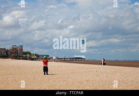 Cleethorpes, Lincolnshire, UK. 16th June 2019. UK weather. While northern parts of Lincolnshire suffer the remants of flooding, in Cleethorpes in north east Linconshire on Sunday afternoon families were enjoying the sun shine on Cleethorpes sandy beach with The Pier in the background, one little girl flying a kite with her family, others riding the donkeys and the next sheltering from a torrential downpour. Warm with 18 degrees. - Stock Photo