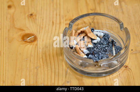 Nuremberg, Germany - June 6, 2019: Unhealthy behavior - an ashtray with cigarette butts, ash and a match standing on a beer table - Stock Photo