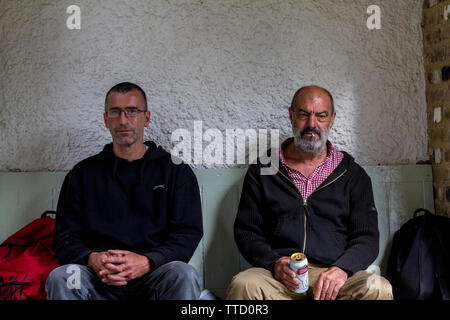 Two homeless men, one from Ireland and the other frmo Spain posing in Rusking Park. The Spanish man (sitting on the right) is smoking a cigarette and - Stock Photo