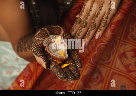 Indian bride holding a diya on her palm - Stock Photo