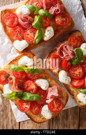 Ciabatta sandwiches with mozzarella, tomatoes, ham and basil close-up on the table. Vertical top view from above - Stock Photo
