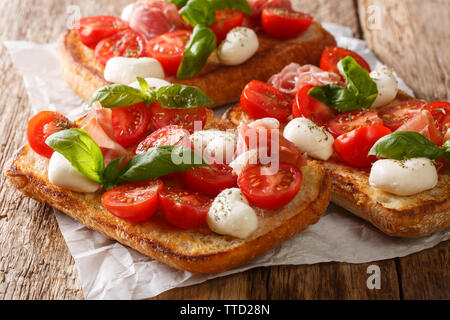 Ciabatta sandwiches with mozzarella, tomatoes, ham and basil close-up on the table. horizontal - Stock Photo