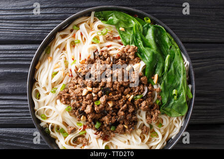 Traditional Chinese Sichuan Dan Dan Noodles with minced meat and greens in a plate on the table. Horizontal top view from above - Stock Photo