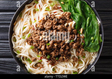 Dan Dan Noodles - Savory and spicy Sichuan noodles served with ground meat closeup on the plate on the table. horizontal top view from above - Stock Photo