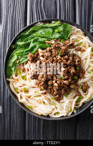 Traditional Chinese Sichuan Dan Dan Noodles with minced meat and greens in a plate on the table. Vertical top view from above - Stock Photo