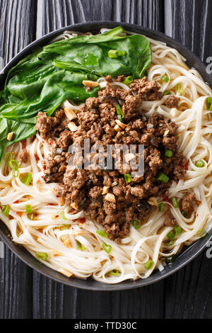Dan Dan Noodles - Savory and spicy Sichuan noodles served with ground meat closeup on the plate on the table. Vertical top view from above - Stock Photo