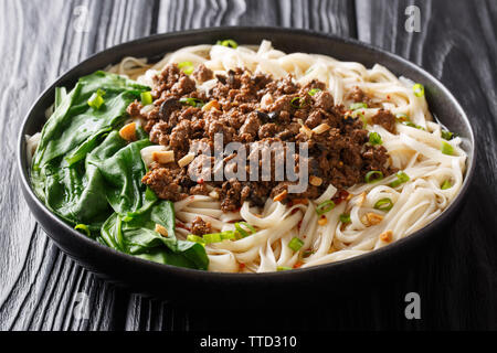 Spicy Dan Dan Noodles with minced meat and herbs served with hot sauce in a plate on the table. horizontal - Stock Photo