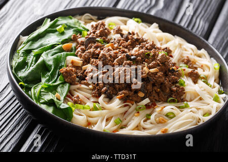 Traditional Chinese Sichuan Dan Dan Noodles with minced meat and greens in a plate on the table. horizontal - Stock Photo