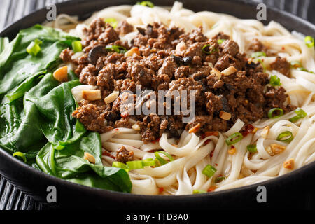 Sichuan Dan Dan Noodles with minced meat and greens closeup in a plate on the table. horizontal - Stock Photo