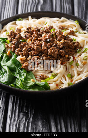 Dan Dan Noodles - Savory and spicy Sichuan noodles served with ground meat closeup on the plate on the table. vertical - Stock Photo