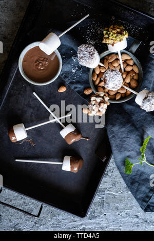 Homemade sweet marshmallow pops dipped in chocolate, sprinkled with pistachios, almonds and grated coconut - Stock Photo