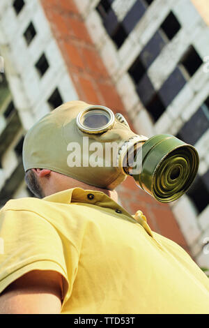 Person in gas mask taken close up on destroyed building background. - Stock Photo