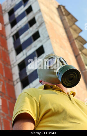Men in gas mask on destroyed building background taken close up. - Stock Photo