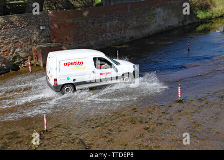 SIDMOUTH, DEVON - APRIL 1ST 2012: A van travels through the ford on the river Sid. - Stock Photo