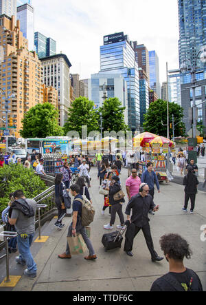 The southwest corner of Central Park at Columbus Circle is always busy with park goers and tourists. - Stock Photo