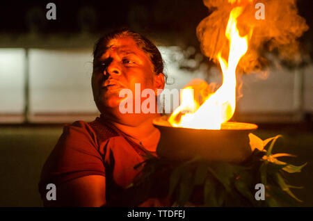 A Woman Holding a Burning Coconut in front of the Shrine in Kataragama, Sri Lanka - Stock Photo