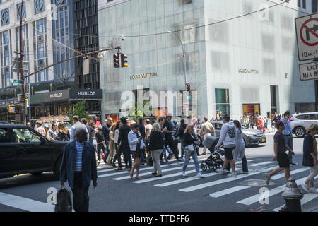 Pedestrians cross the always busy corner of 5th Avenue and 57th Street in midtown Manhattan. - Stock Photo