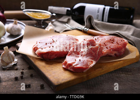 Marbled beef steak with bottle of wine and spices on wooden background