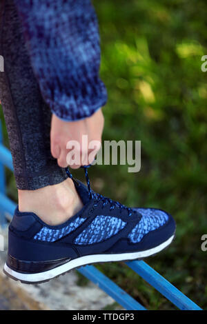 Woman in sportswear tying shoelaces on sneakers outdoor close-up - Stock Photo