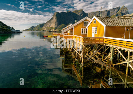 Beautiful view of scenic Lofoten Islands archipelago winter scenery with traditional yellow fisherman Rorbuer cabins in the historic village of Sakris - Stock Photo