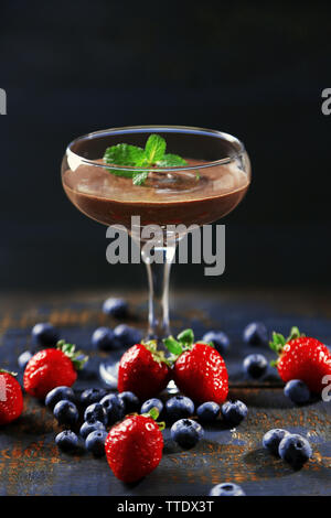 Chocolate dessert in glass and fresh berries on color wooden background - Stock Photo
