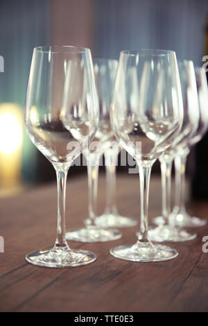 Empty wine glasses with bottle on wooden table against blurred background - Stock Photo