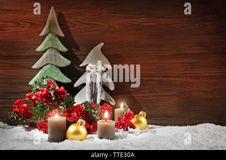 Fir trees, candles and balls with brunch of holly berries in a snow over wooden background, still life - Stock Photo