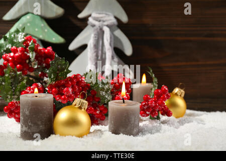 Fir trees, candles and balls with brunch of holly berries in a snow over wooden background, close up - Stock Photo