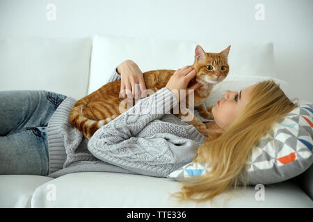 Young woman with red cat laying on sofa - Stock Photo