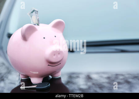 Piggy money box with cash and key on car bonnet at the street - Stock Photo