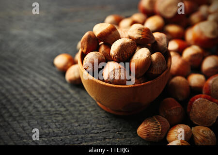 Scattered hazelnuts and acorns on grey wooden table - Stock Photo