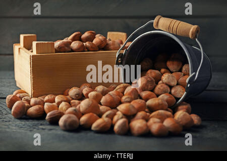 A metal bucket and scattered hazelnuts on the wooden table, close-up - Stock Photo