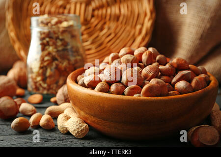 Hazelnuts, walnuts, peanuts in the bowl and glass jar on the table - Stock Photo