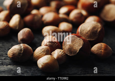 Scattered hazelnuts and acorns on grey wooden table, close-up - Stock Photo
