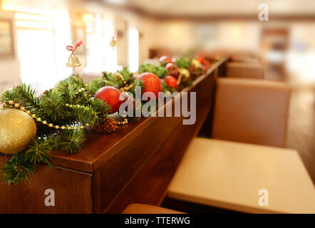 Christmas decorations on wooden desk in cafe - Stock Photo