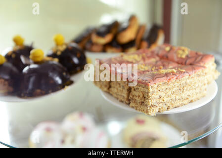 Delicious cakes on glass shelf in confectionery close up - Stock Photo