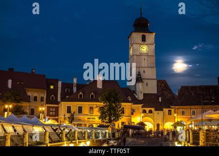 Sibiu City, Romania - 16 June 2019. Twilight image of Council Tower with moon and Small Square (Piata Mica) landmark of Sibiu town in Transylvania Rom - Stock Photo