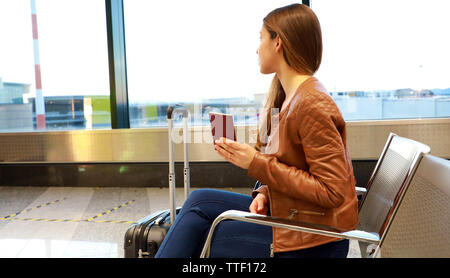 Beautiful young woman looking out window while waiting boarding on aircraft with passport in her hand - Stock Photo