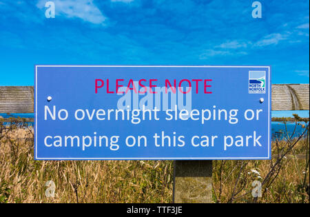 Sign attached to fence near Cromer beach: 'No overnight sleeping or camping on this carpark'. Erected by North Norfolk District Council. England, UK. - Stock Photo