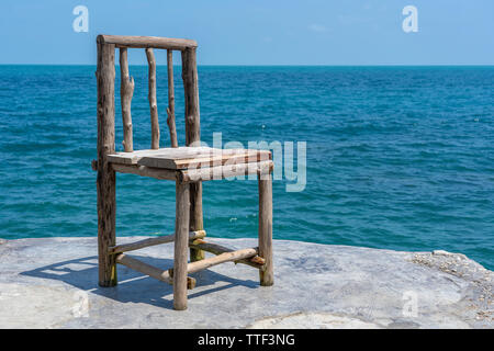 Wooden chair in empty cafe next to sea water in tropical beach. Close up. Island Koh Phangan, Thailand - Stock Photo