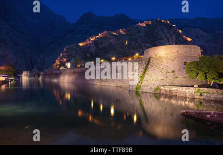 Kampana Tower and wall of Kotor old town reflecting in water at dusk, Montenegro - Stock Photo