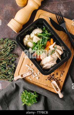 High angle view of meat with vegetables in container on cutting board - Stock Photo