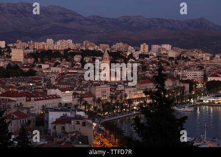 High angle view of buildings in town against mountains at dusk - Stock Photo
